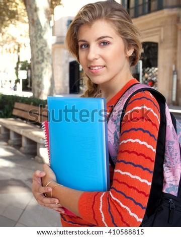 Portrait of beautiful college student smiling at camera in a city avenue with trees and stone pavement, carrying school folders and a backpack, smiling outdoors. Student lifestyle, street exterior. - stock photo