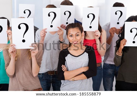 Portrait of beautiful college student surrounded by classmates holding question mark signs in classroom - stock photo