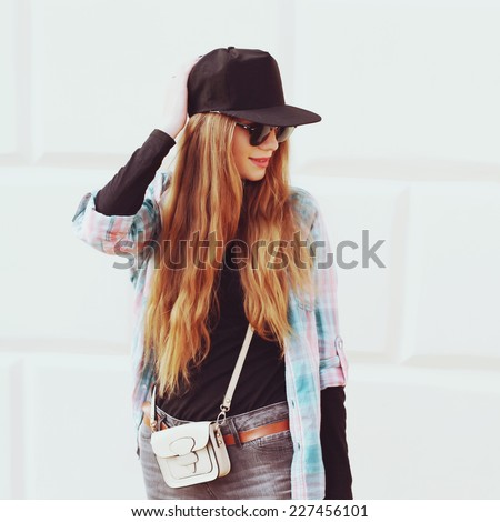 Portrait of beautiful cool girl gesturing in hat and sunglasses over grunge wall. Photo toned style Instagram filters. - stock photo