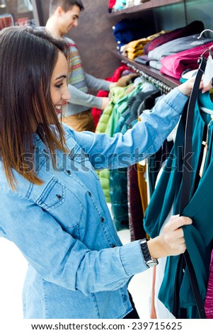 Portrait of beautiful couple shopping in a clothes shop. - stock photo