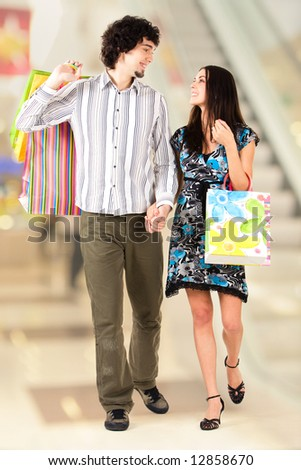 Portrait of beautiful couple walking with shopping bags - stock photo