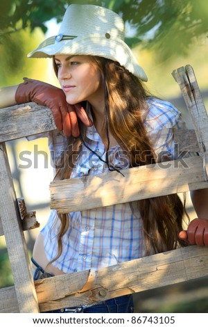 Portrait of beautiful cowgirl in stetson next to wooden fence - stock photo