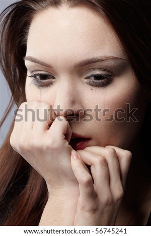portrait of beautiful crying girl with smeared mascara hiding her face in hands