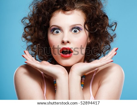 portrait of beautiful curly brunette girl on blue - stock photo