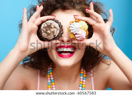 portrait of beautiful curly brunette girl with two tarts - stock photo