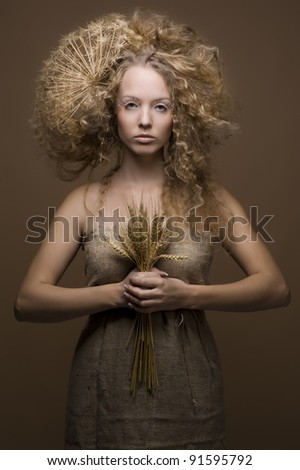 portrait of beautiful curly girl with wheat on a beige background - stock photo