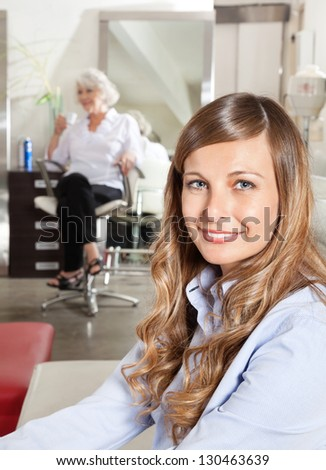 Portrait of beautiful customer sitting with woman in background at hair salon - stock photo