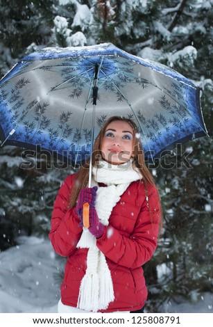 Portrait of beautiful, cute young woman standing under an umbrella. Closeup. - stock photo