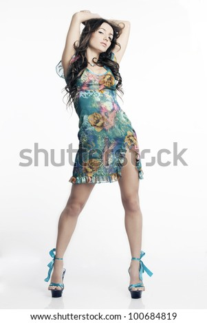 Portrait of beautiful dancing woman with long legs in a dress on a white background