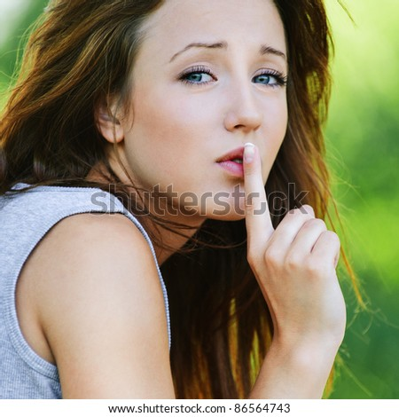 Portrait of beautiful dark-haired girl wearing grey t-shirt, holding finger near lips at summer green park. - stock photo
