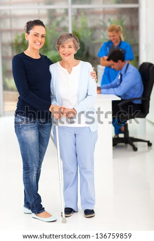 portrait of beautiful daughter taking her elderly mother to doctor - stock photo