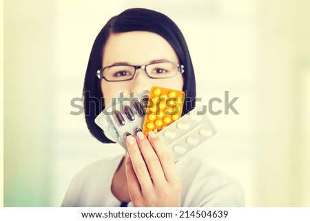 Portrait of beautiful doctor or nurse holding prescription drugs isolated over white background - stock photo