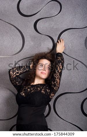 portrait of beautiful dreamy woman in a black dress on a gray background