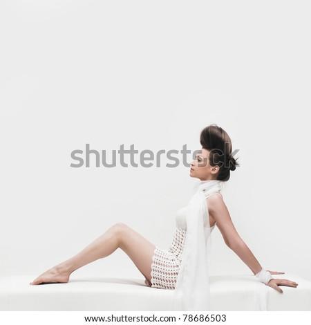 portrait of beautiful elegant woman sitting in white dress - stock photo