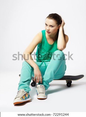 portrait of beautiful extreme girl with skateboard on gray - stock photo