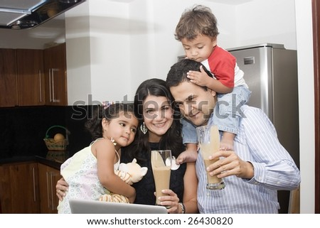 Portrait of beautiful family cooking in kitchen, dad, mom and little daughter