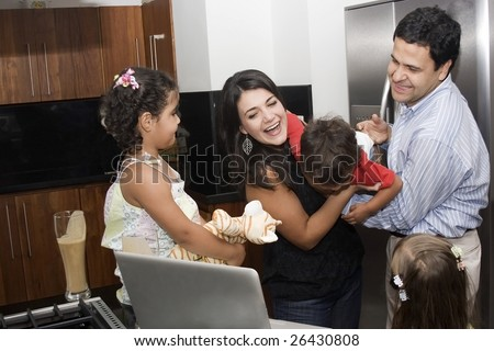 Portrait of beautiful family playing in kitchen, dad, mom, daughters and little boy