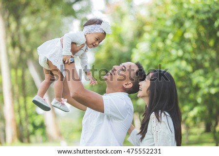 portrait of Beautiful family with cute baby in the park having fun together