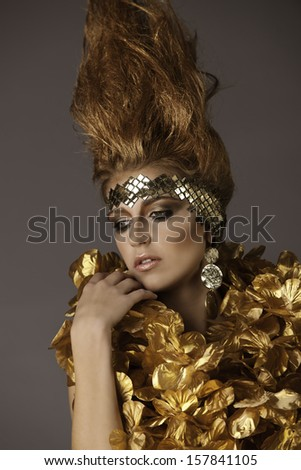 Portrait of beautiful fantasy warrior princess with headdress, bronze flame hairstyle wearing golden flowers and tribal earrings - stock photo