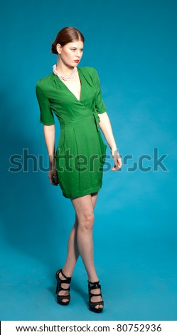 Portrait of beautiful fashion model in green dress on blue background - stock photo