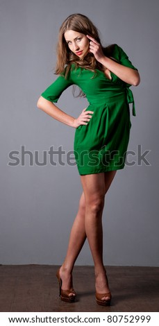 Portrait of beautiful fashion model in green dress on grey - stock photo