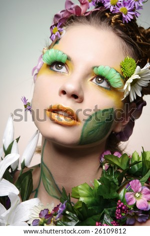 Portrait of beautiful fashion model wearing costume made of flowers. - stock photo