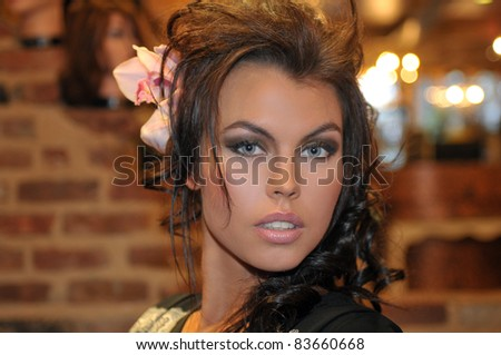 portrait of beautiful Fashion runway model with glamor make-up orchid flower in a hair - stock photo