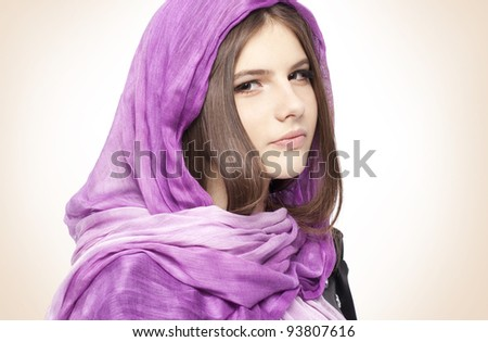 Portrait of beautiful fashion young girl teenager in lilac scarf healthy clean skin glossy brown hair closeup in studio on beige background - stock photo