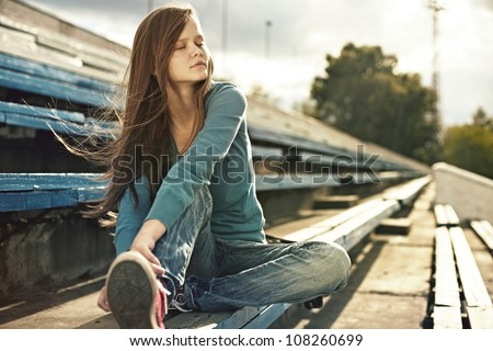 portrait of  beautiful fashionable girl in the stadium on summer day - stock photo