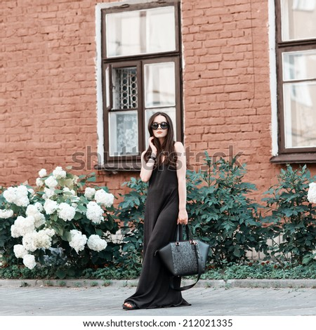 Portrait of beautiful fashionable woman in a dress with a bag of glasses around the house with flowers - stock photo