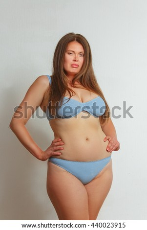 Portrait of beautiful fat woman in underwear or lingerie posing with her hands on hips. Red haired lady looking at camera in studio. - stock photo