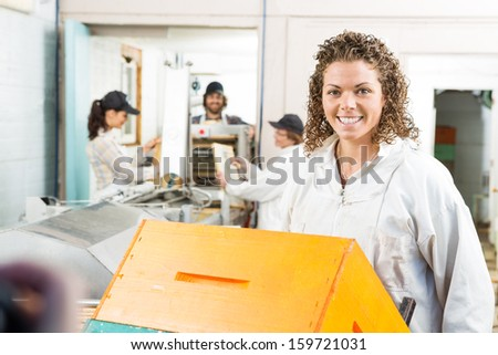 Portrait of beautiful female beekeeper with stacked honeycomb crates in beekeeping factory