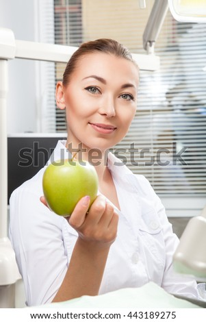 Portrait of beautiful female doctor in white uniform smiling and holding green fresh ripe apple. Face expressions, emotion, health care, medicine, occupation.