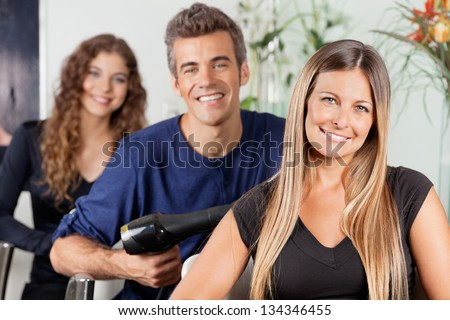 Portrait of beautiful female hairstylist sitting with colleagues in salon - stock photo