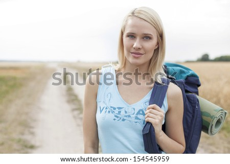 Portrait of beautiful female hiker with backpack standing on field - stock photo