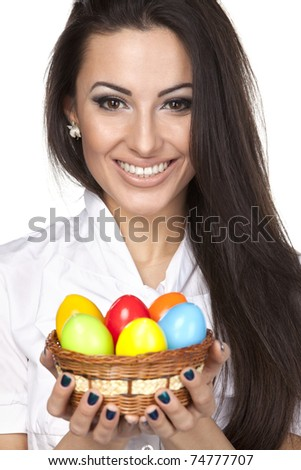 Portrait of beautiful female holding basket with Easter eggs isolated on white background