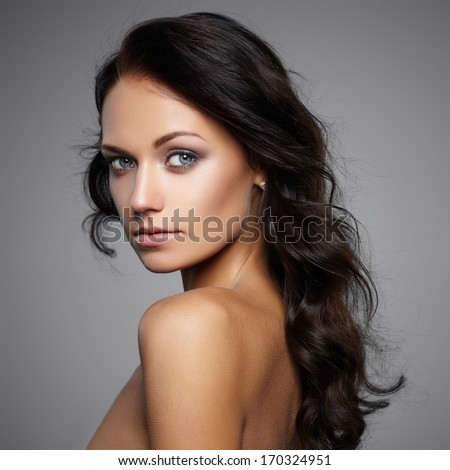 Portrait of beautiful female model on gray background - stock photo