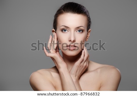 Portrait of beautiful female model on gray background - stock photo