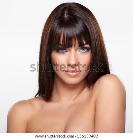 Portrait of beautiful female model on grey background - stock photo