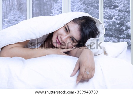 Portrait of beautiful female model smiling at the camera while lying on the bed under blanket with winter background on the window - stock photo