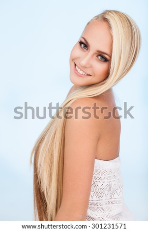 Portrait of beautiful female model with long hair on blue background - stock photo