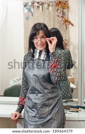 Portrait of beautiful female owner of parlor standing in salon - stock photo