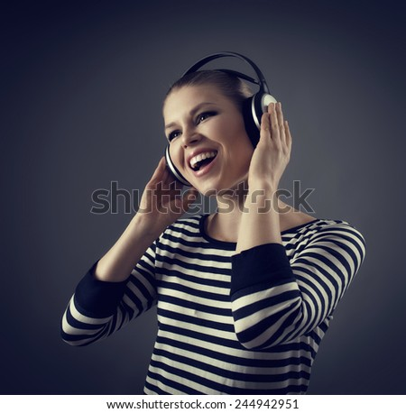 Portrait of beautiful female performer wearing headset singing song in recording studio. Young cheerful Caucasian woman enjoying dynamic music.  - stock photo