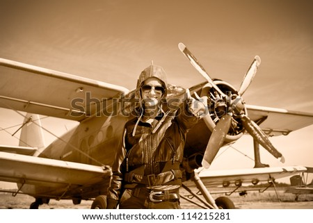 Portrait of beautiful female pilot with plane behind. Sepia photo. - stock photo