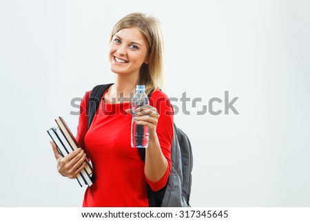 Portrait of beautiful female student holding water bottle.Healthy refreshment for student - stock photo