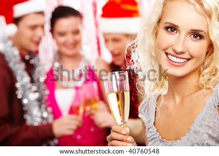 Portrait of beautiful female with champagne looking at camera and smiling - stock photo