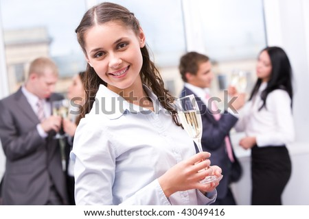 Portrait of beautiful female with champagne looking at camera and smiling