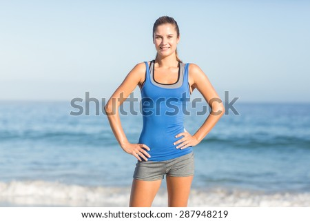 Portrait of beautiful fit woman looking at camera with hands on hips at the beach - stock photo