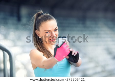 Portrait of beautiful fitness woman taking selfie with phone camera. Healthy woman training and taking pictures - stock photo