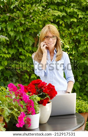 Portrait of beautiful flower shop owner working on laptop while using mobile. Small business.  - stock photo